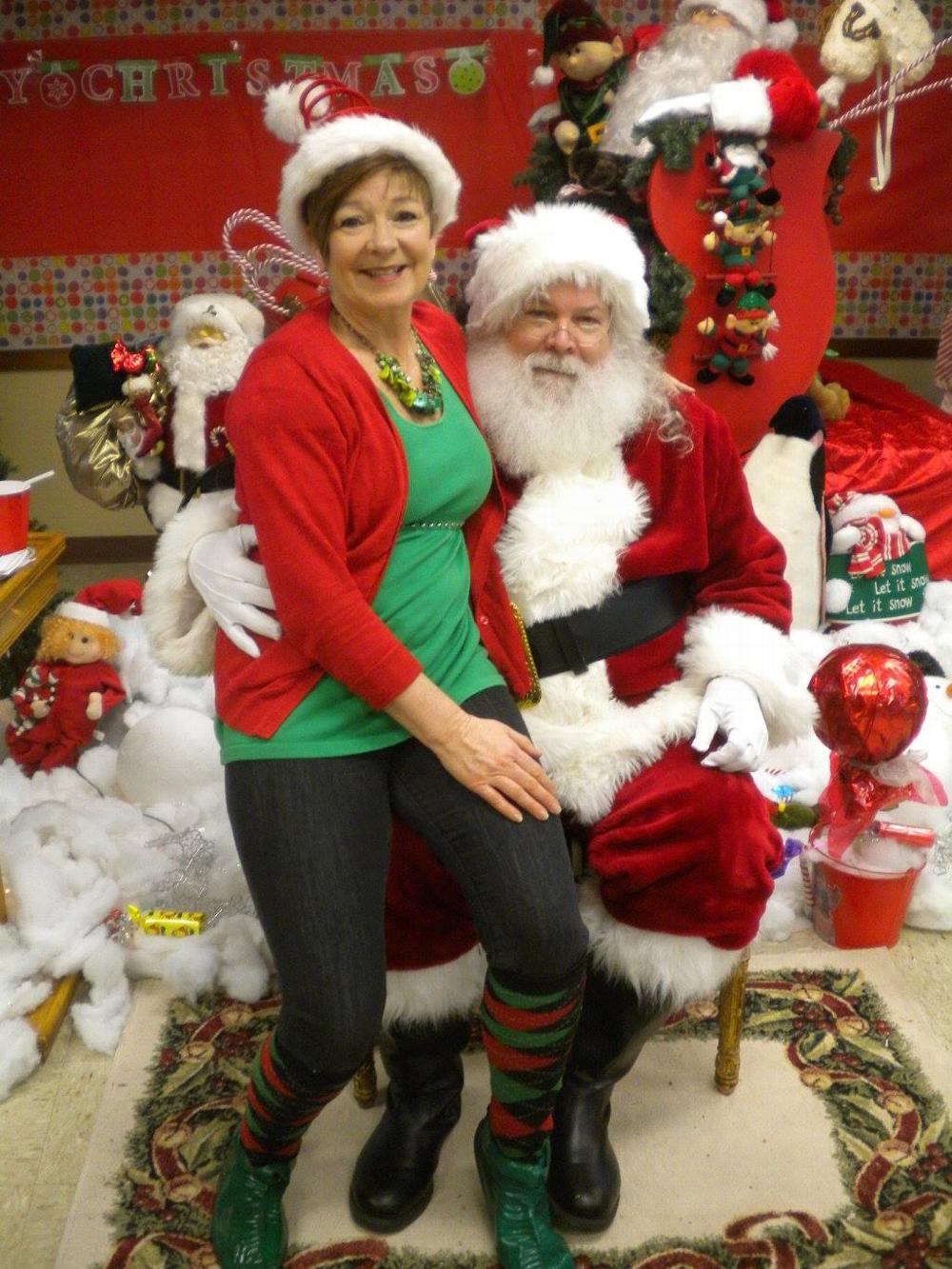 Elf Luanne Cummings with Santa.